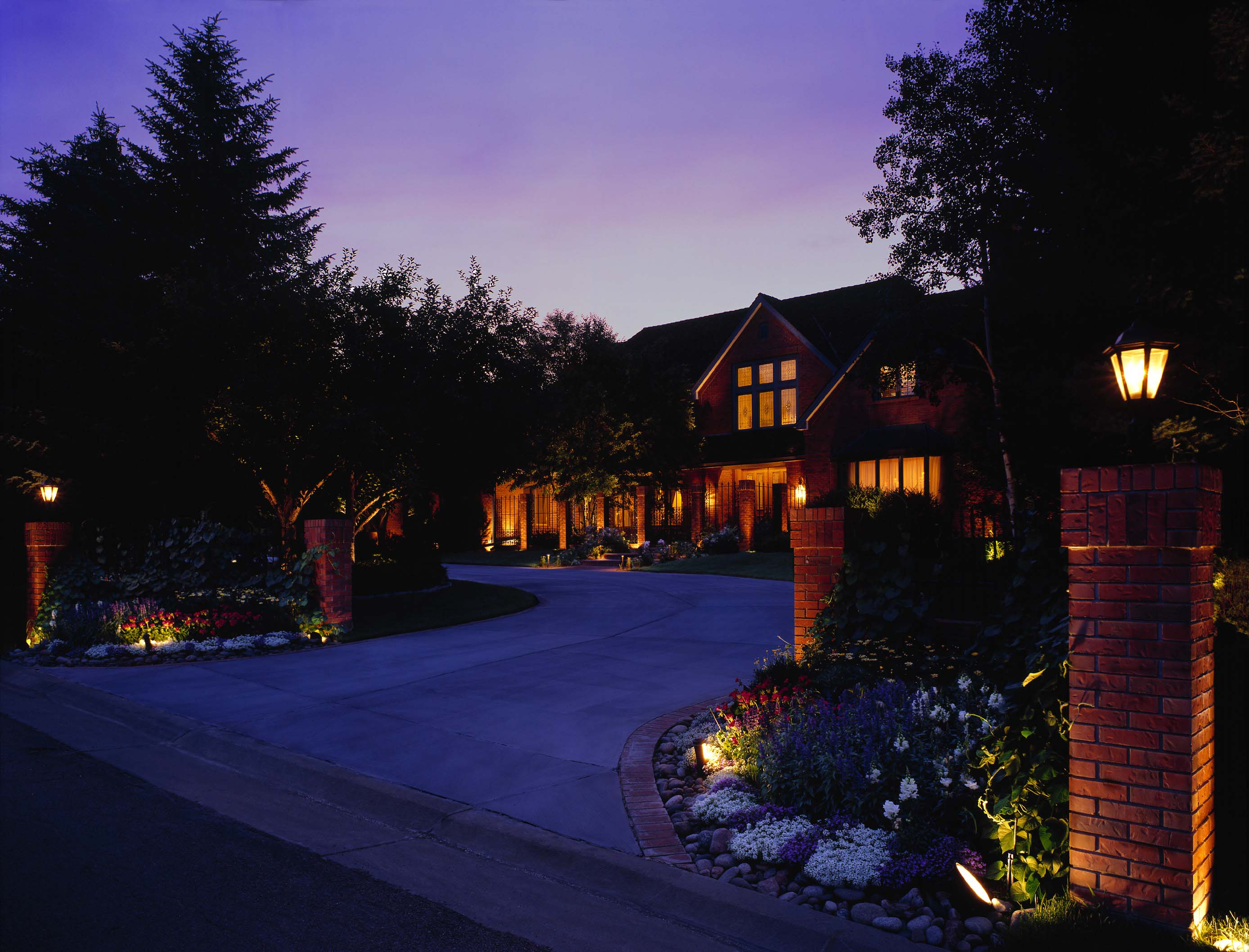 Cherry Hills Farm/Arapahoe County landscape/architectural lighting. For this project, the homeowners wanted to illuminate primarily the beautiful brick entrance columns and flower beds lining the circular drive. Here you can see how the low voltage lighting system really brings out the coloring and texturing of the red brick – as well as the flowers.