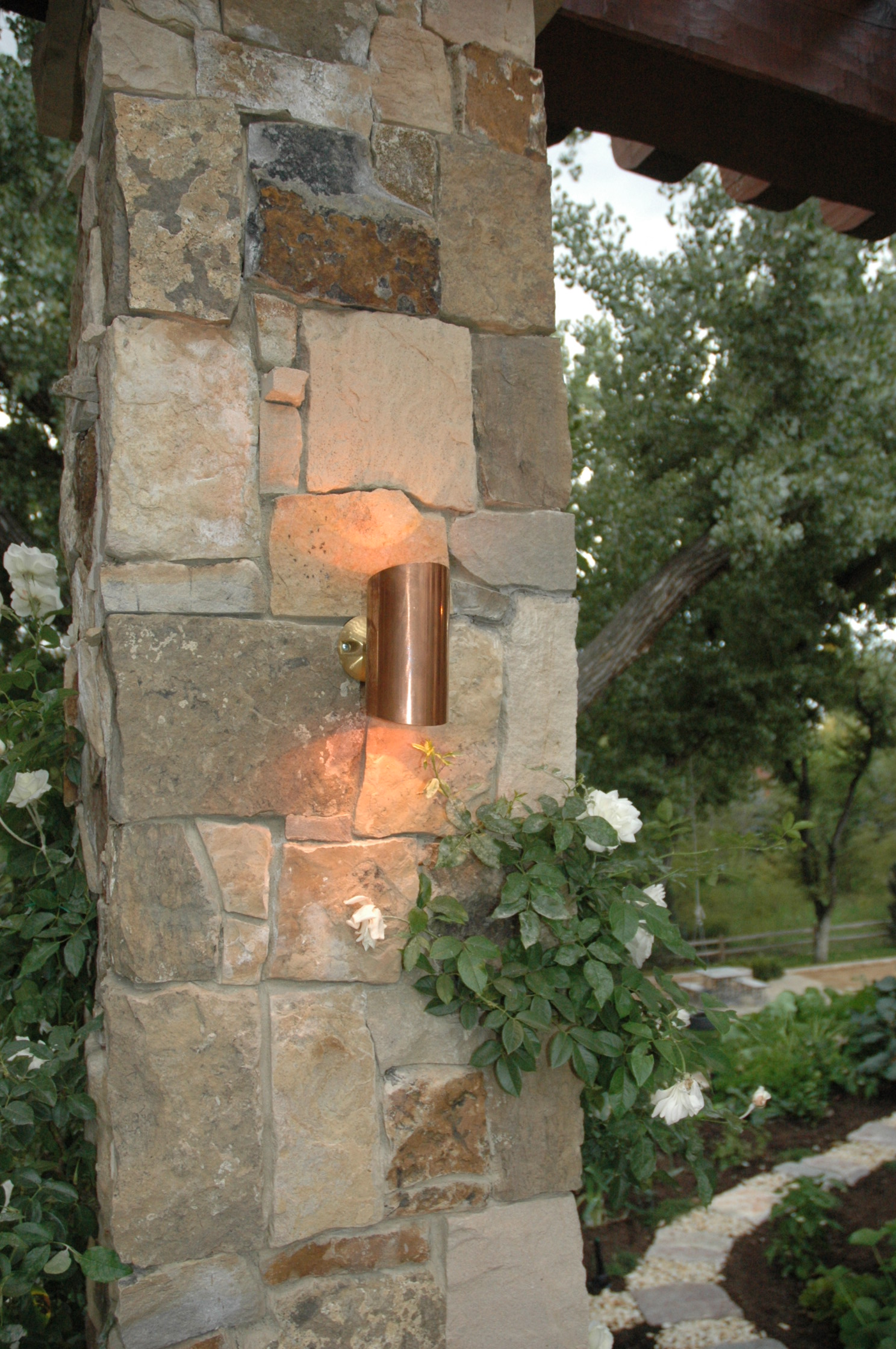 Cherry Hills Village Tuscan-inspired pergola. At this Tuscan-inspired pergola in Cherry Hills Village, the only lighting the homeowners had for evening dining was a candle candelabra over the table. Outdoor Lighting Perspectives (OLP) installed these 20W quartz halogen copper/brass BB-15 sconce fixtures to both up-light and down- light the beautiful stone columns as well as the vines growing on the pergola structure above. All of this lighting is controllable via one of OLP's intelligent switches that was installed inside the kitchen.
