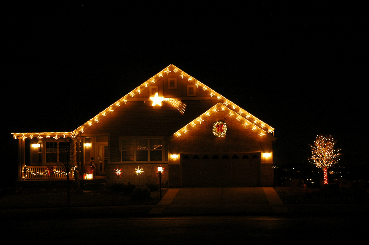 Holiday lighting at Heritage Eagle Bend home - Arapahoe County, CO. This home was a winner of the community holiday lighting contest a few years ago. Festive snowflake light links outline the roof line, a lighted wreath hangs over the garage, multi-color starbursts line the sidewalk, and a shooting star with motion effects appears to be streaking across the evening sky.