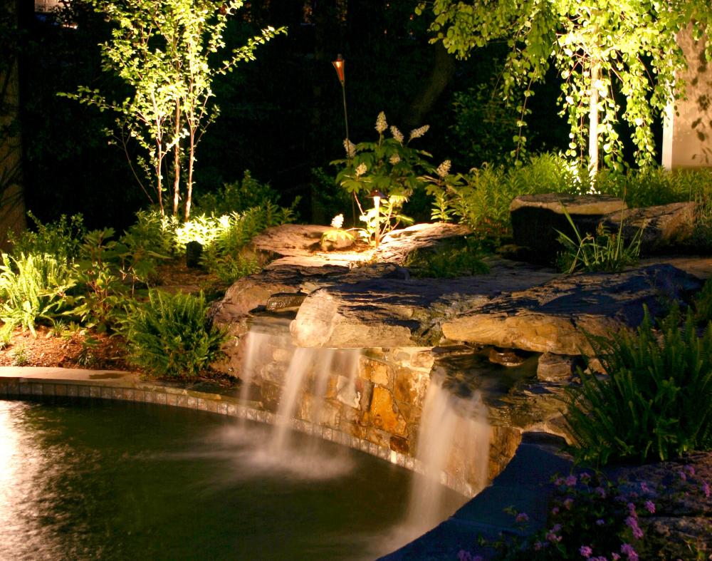 Landscape waterfall lighting Northern Ohio. This custom water feature gets an added lift with illuminating the landscaping around it and also illuminating the water feature itself.