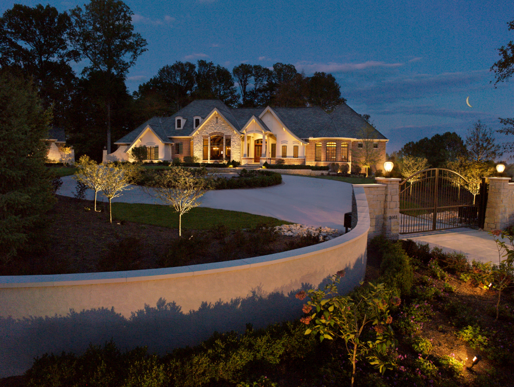 "Cleveland outdoor architectural and landscape lighting. Imagine if this wonderfully well lit home did not have the majestic entrance illuminated? The lighting design at this home uses driveway lighting, parthway lighting, and barrier wall lighting to ""light the way""."