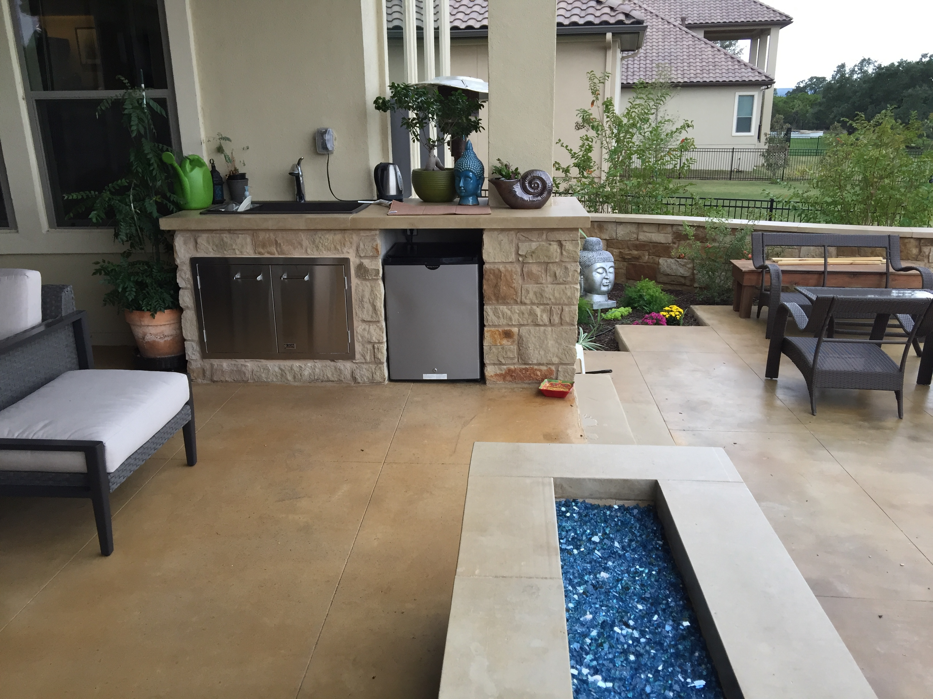 This Contemporary Austin Patio In Steiner Ranch Includes A Custom Outdoor  Kitchen And A Rectangular Fire Pit That Utilizes Blue Glass.