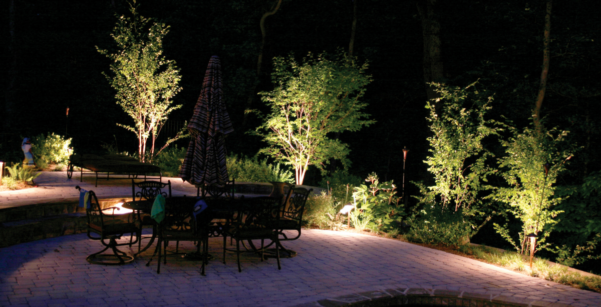 St. Louis patio lighting and garden lighting. This path lighting serves two purposes. First, it lights up the beautiful garden and trees surrounding this patio. But secondly, it lights up the patio so the family can enjoy their outdoor living area at night.
