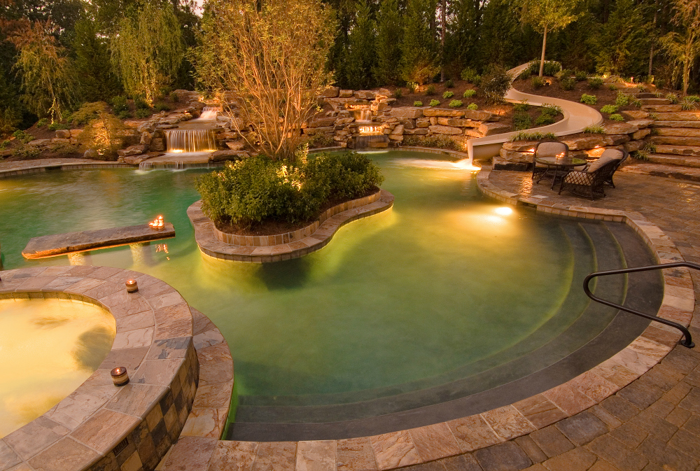Misty water feature lighting St. Louis. As mist lazily adorns this large water feature, this family can enjoy their outdoor living area at night.