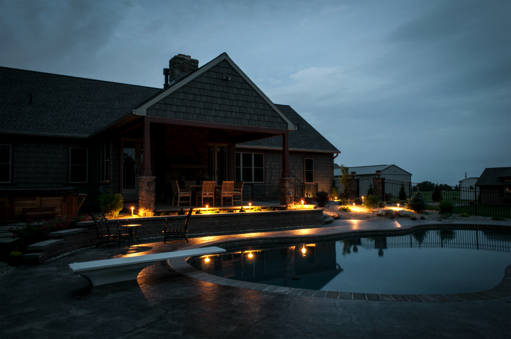 Add Lighting to enhance and not FLOOD your outdoor space. Enjoy your pool well into the evening without feeling like you are swimming under the flood lights with some well placed low voltage outdoor lights.  Here we used path lights to separate the outside patio from the swimming pool area.
