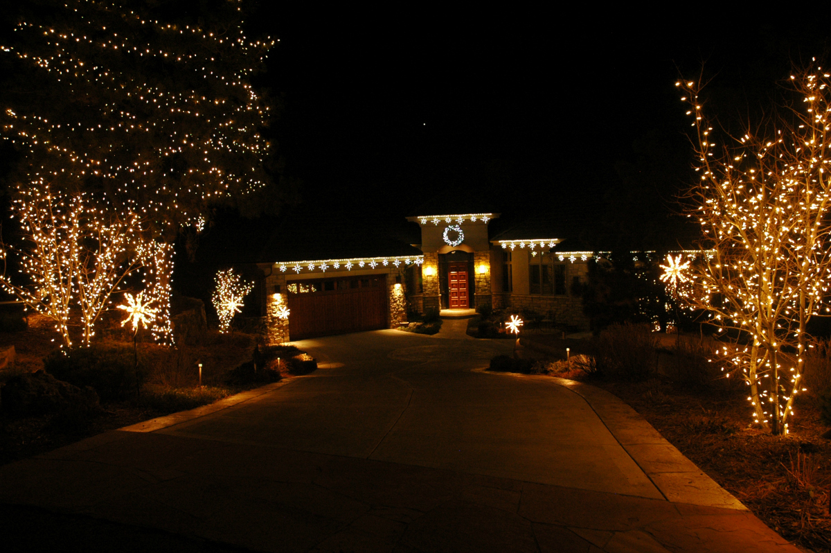 Holiday lighting at Castle Pines Village home - Douglas County, CO. Snow flake light links outline the roof line, lighted star bursts light the driveway, and mini-lights on the trees and shrubs complete the design at this Castle Pines Village home.