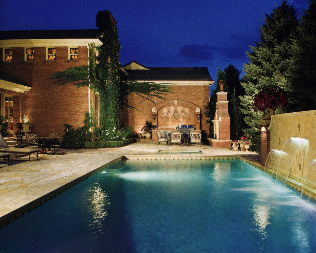 Cherry Hills Village Pool and Patio Lighting. This wonderful back yard pool and patio area is enhanced by up-lighting the brick façade of the house and tree with well lights, by down-lighting the brick columns flanking the pool with copper sconce lights, and illuminating the pool deck and gardens with copper path lights.