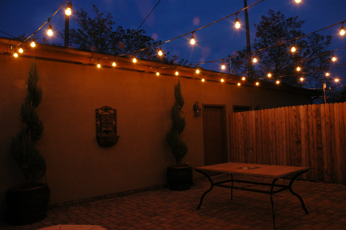 Festival lighting in Denver townhome courtyard. This festival lighting installation is certainly not a few strands of hastily strung lights on a string. This installation is professionally designed and installed using 5 strings and over 40 bulbs. The lights are can be dimmed and brightened using the dimmer switch we installed.