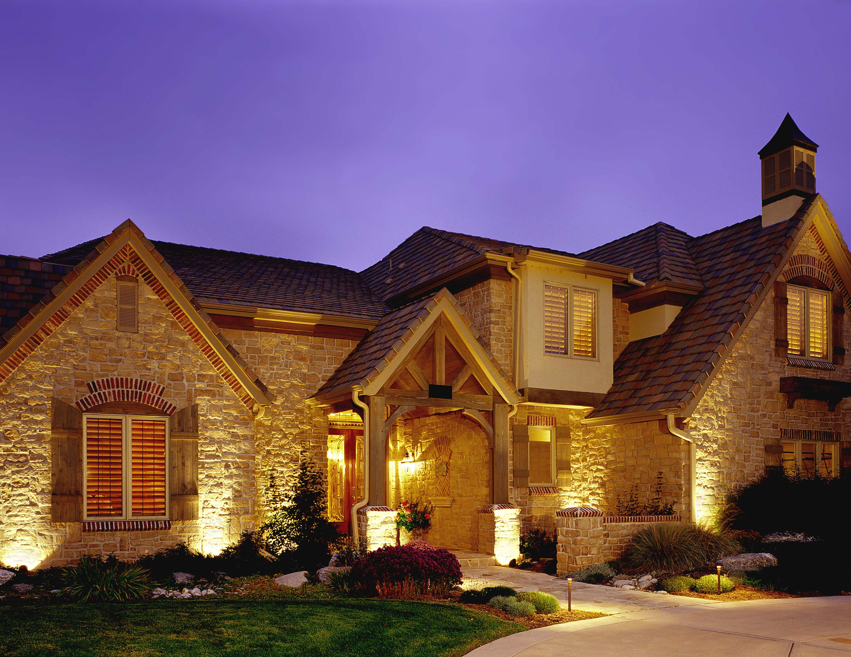 The Preserve in Greenwood Village home with outdoor architectural lighting. This house exemplifies Colorado architecture and it comes to life after dark with Outdoor Lighting Perspectives' (OLP) low voltage quartz halogen lighting system. Notice how the natural stone and wood beams are warmly illuminated by up-lighting the façade of the house with well lights.