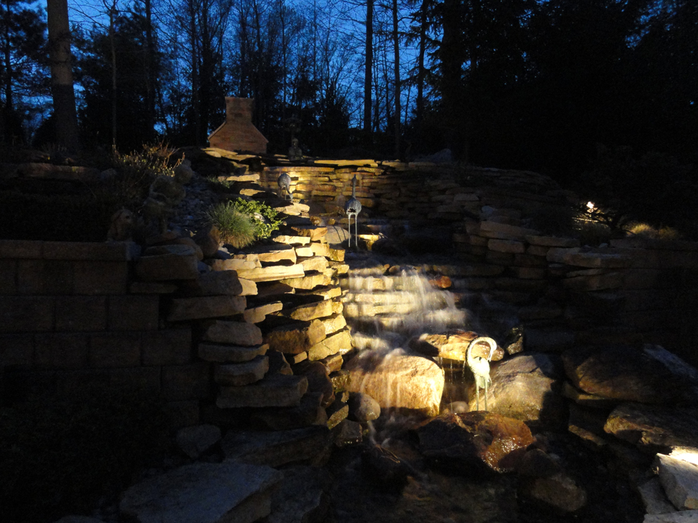 Water Features Glow with Underwater Lighting. This custom waterfall is now magnificent at night with the addition of underwater lighting. Using lights in the water and spot lights shining from the surrounding areas, we made this structure the number one focal point of the yard.