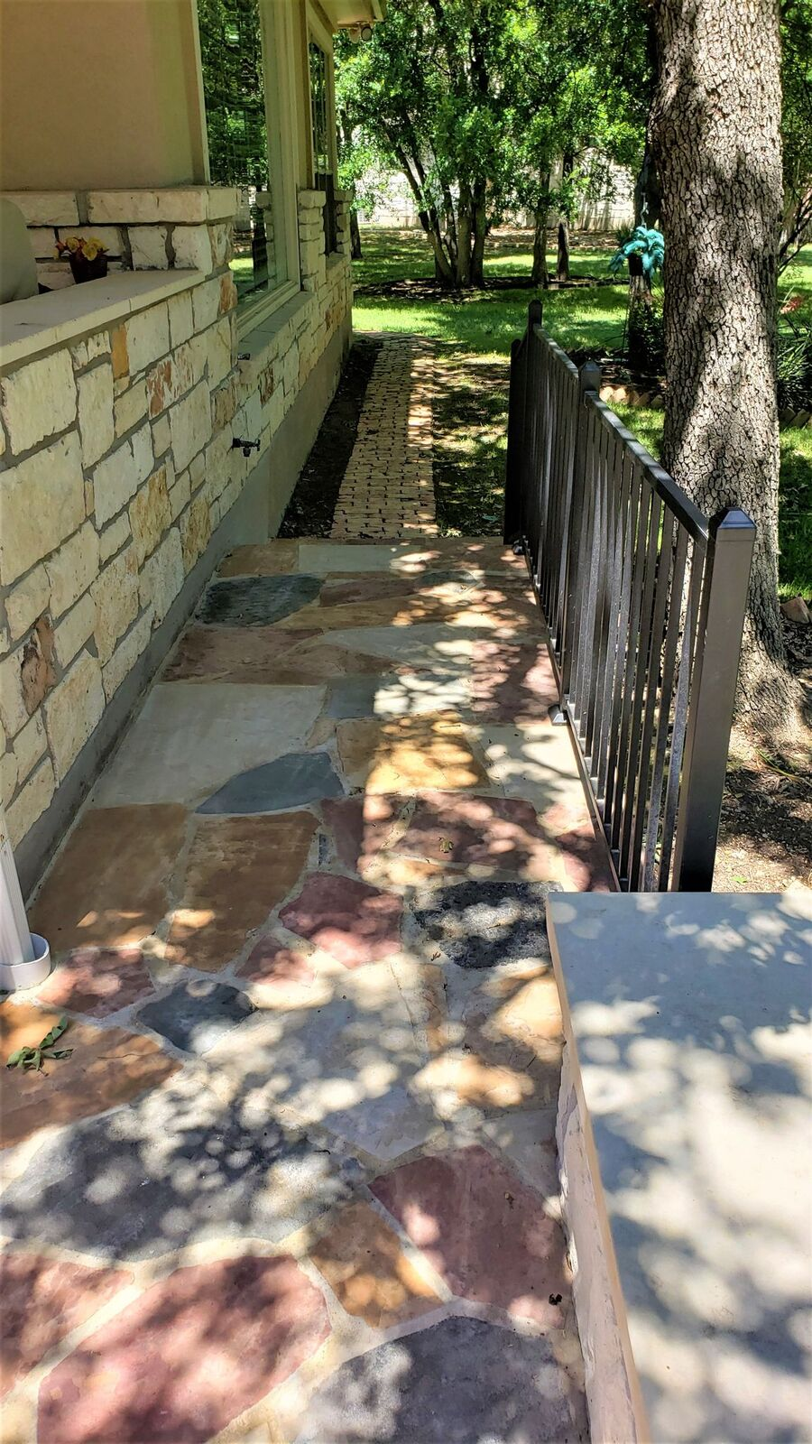Extended-side-yard-area-of-flagstone-patio-with-railing