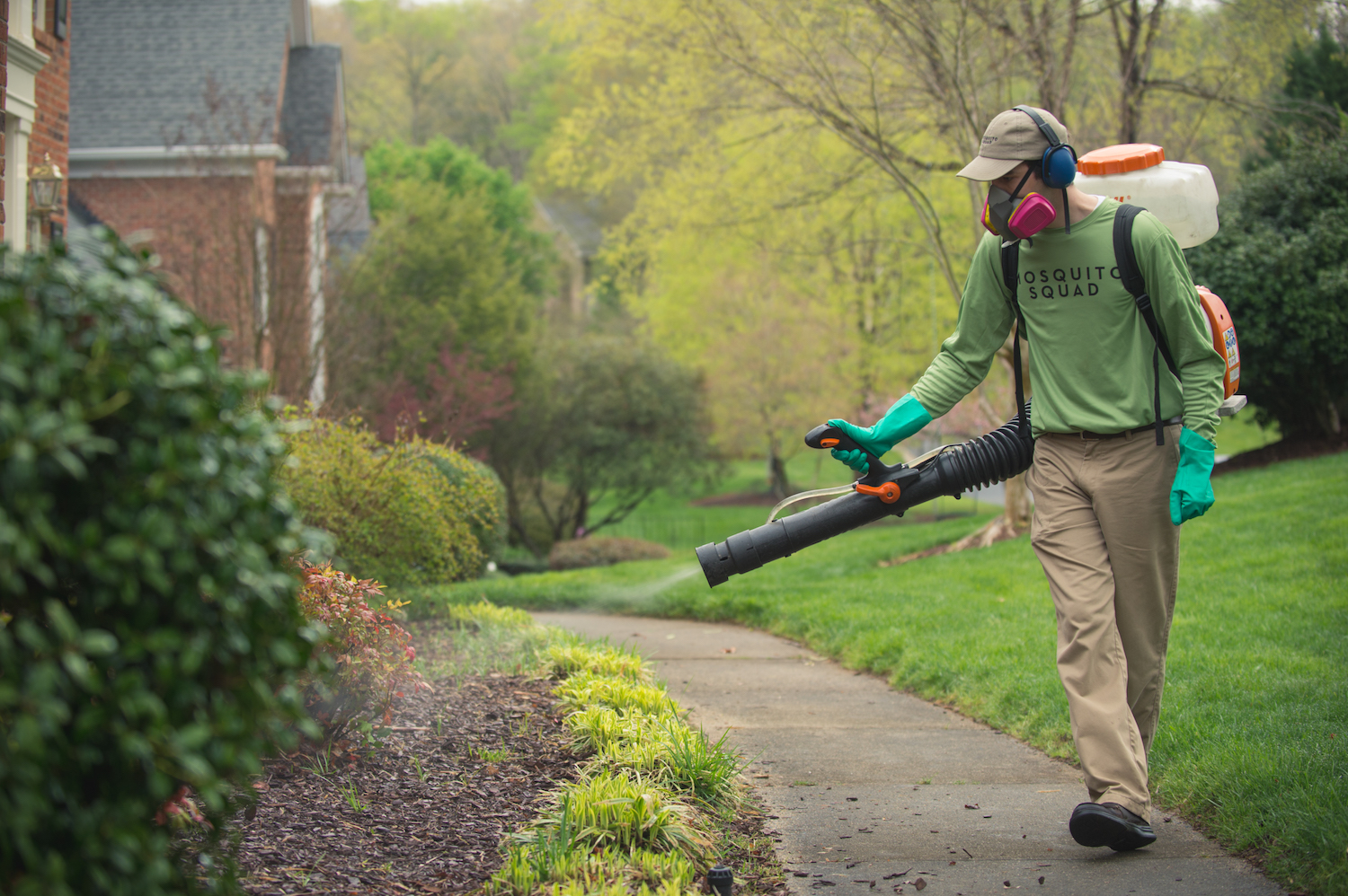 Mosquito Squad employee spraying to get rid of mosquitoes