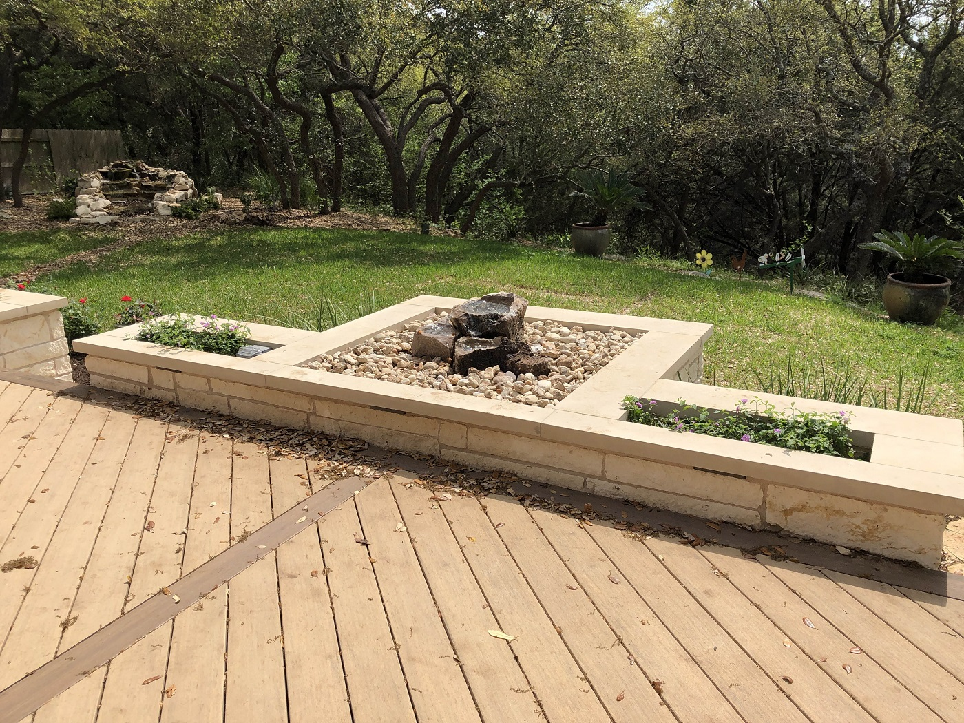 Stone-planters-with-a-custom-water-feature-surround-the-new-deck