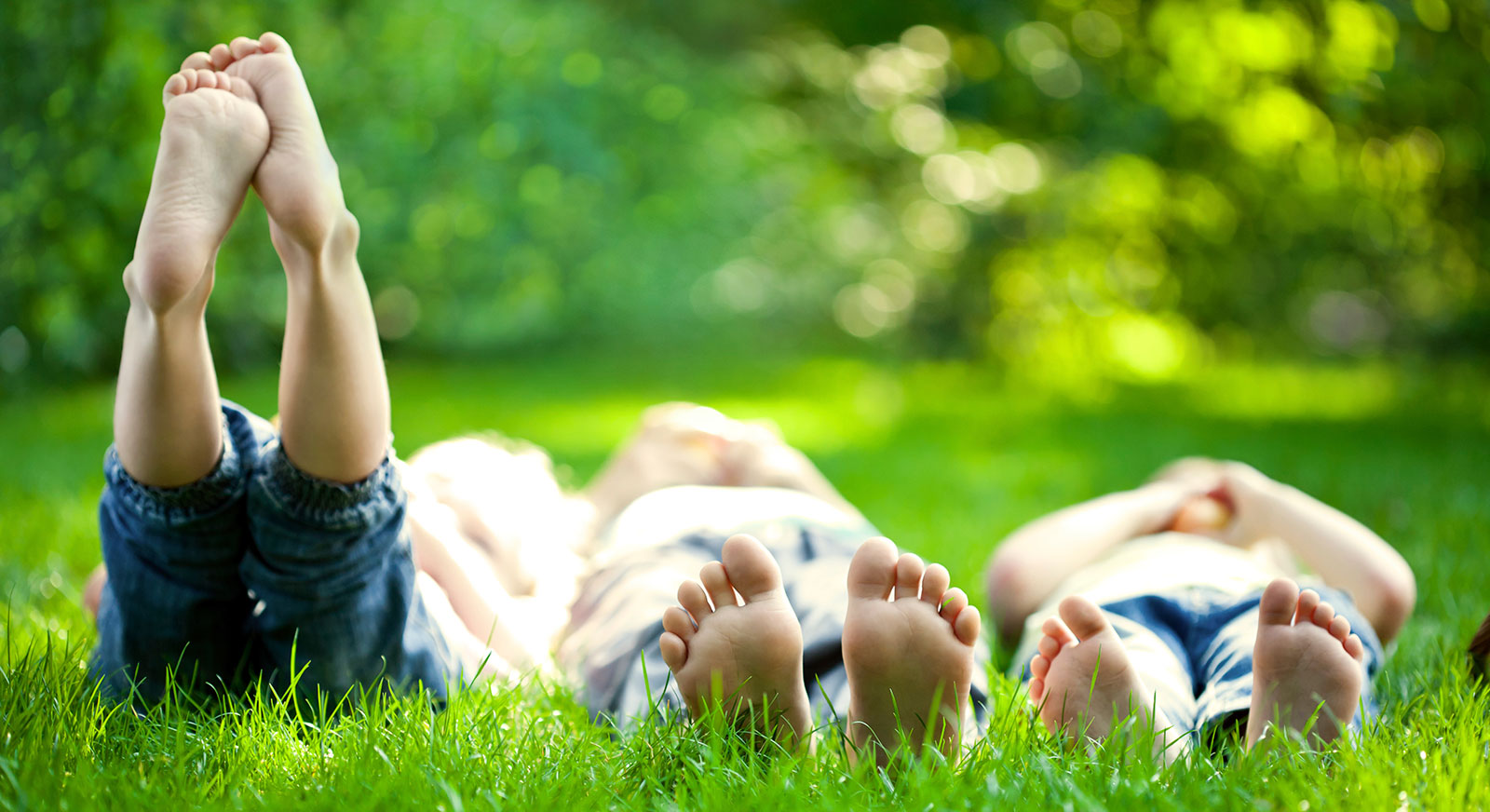 Family laying in grass with feet in the air