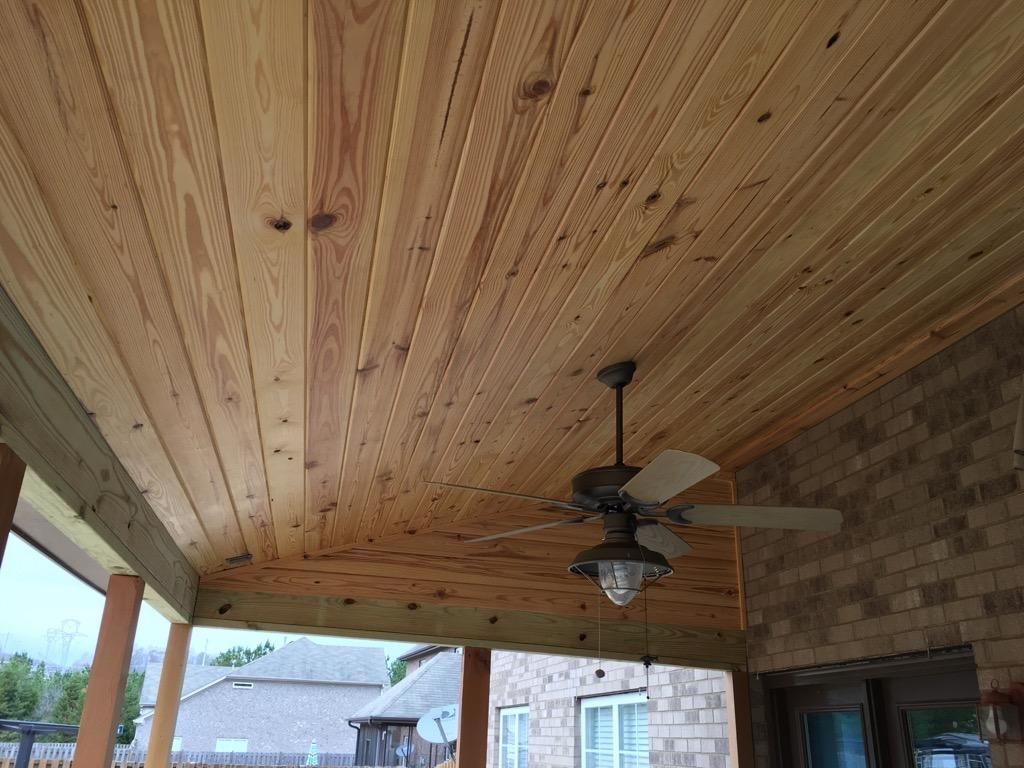 The-covered-porch-interior-features-a-stunning-knotty-pine-ceiling