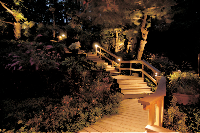 Deck lighting illuminates stairs and surrounding landscape